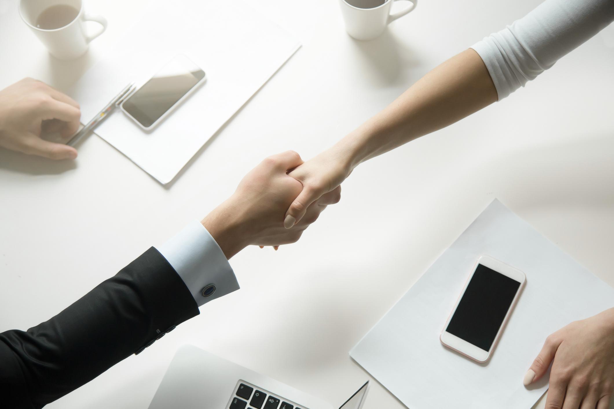 Draufsicht auf einen Händedruck zwischen Mann und Frau