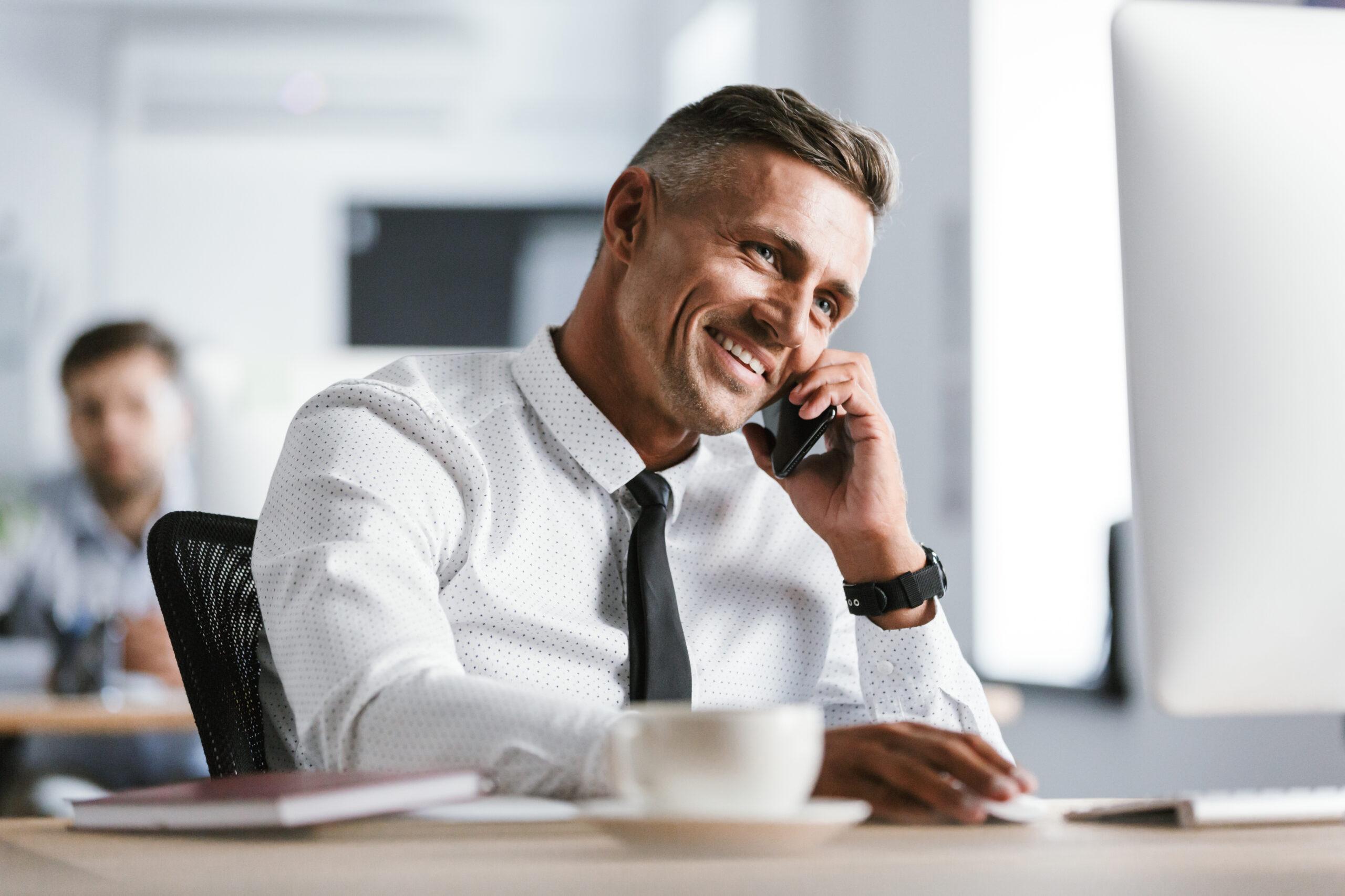 Bild der europäischen erwachsenen Mann 30s trägt weißes Hemd und Krawatte sitzen am Schreibtisch im Büro von Computer und sprechen auf Smartphone